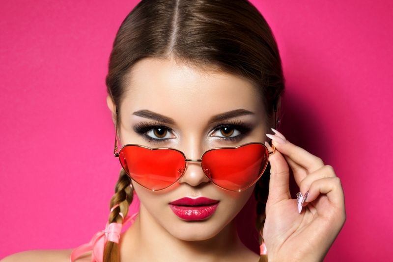 Mujer joven con gafas de sol en forma de corazón