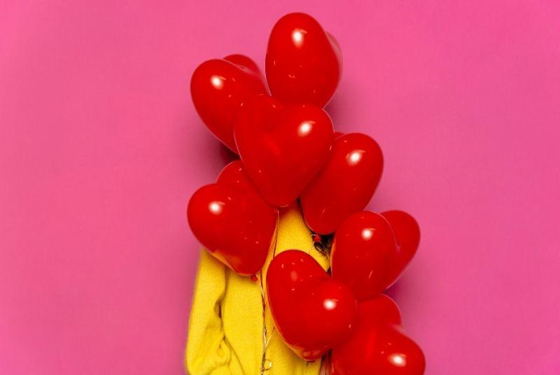 Mujer joven con globos en forma de corazón por San Valentín